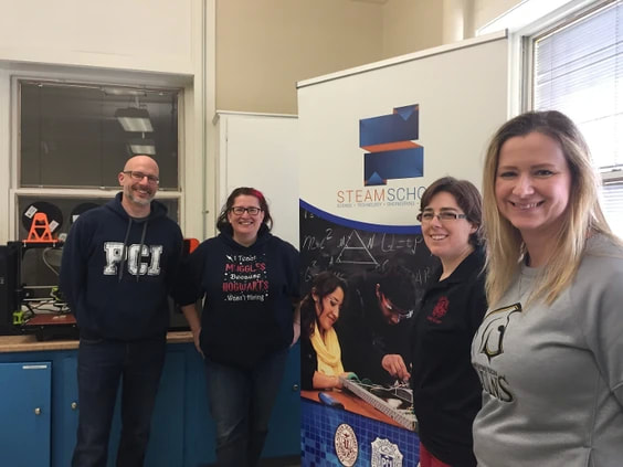 four teachers standing in front of STEAM School banner