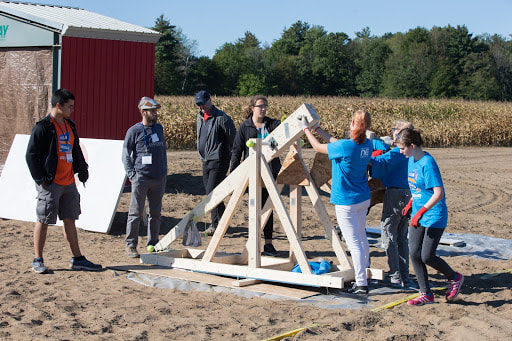 group of people stand around a trebuchet