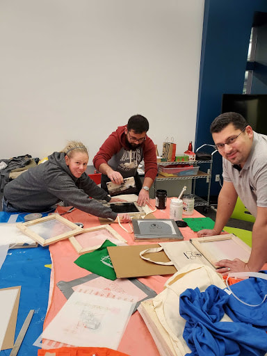 three teachers helping each other silk screen tote bags